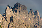 Spotlit by sunset, the Pala Dolomites (Pale di San Martino) soar majestically above the mountain resort of San Martino di Castrozza, seen from Passo Rolle, in Trentino-Alto Adige/Südtirol region of Italy, Europe. 200 million years ago, Triassic coral reefs fossilized into Dolomite. Collision of tectonic plates lifted the Dolomites within the Southern Limestone Alps. UNESCO honored the Dolomites as a natural World Heritage Site in 2009.