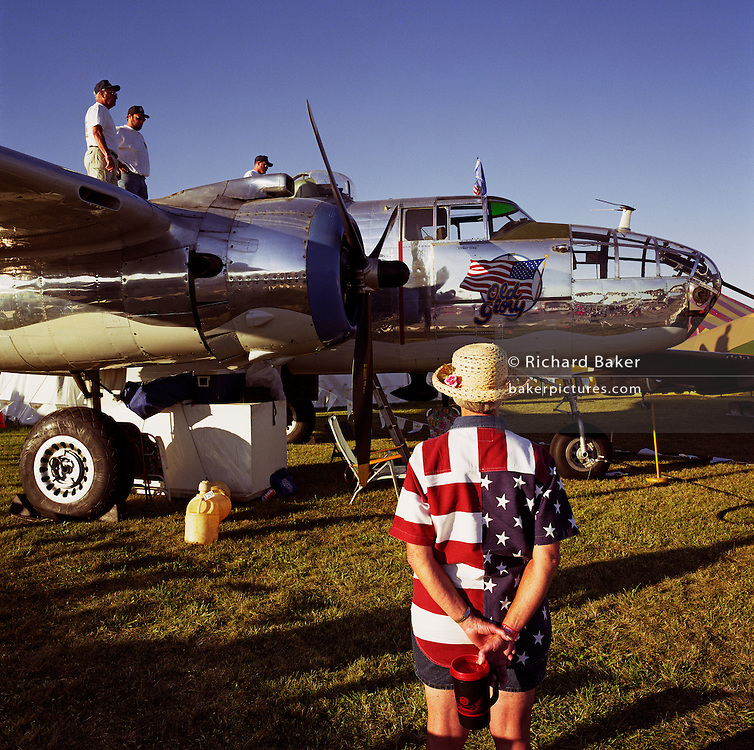 Known as 'Old Glory', a polished silver Boeing Mitchell B-25 is refuelled in readiness for a display flight at Oshkosh Air Venture, the world?s largest air show in Wisconsin USA. In afternoon light, a lady in a stars and stripes shirt stands arms behind her back admiring the lovingly restored polished twin-engine bomber, the most heavily armed airplane of the second world war used for high and low-level bombing, strafing, photoreconnaissance, submarine patrol and fighter. Close to a million populate the mass fly-in over the week, a pilgrimage worshipping all aspects of flight. The event annually generates $85 million in revenue over a 25 mile radius from Oshkosh. Picture from the 'Plane Pictures' project, a celebration of aviation aesthetics and flying culture, 100 years after the Wright brothers first 12 seconds/120 feet powered flight at Kitty Hawk,1903