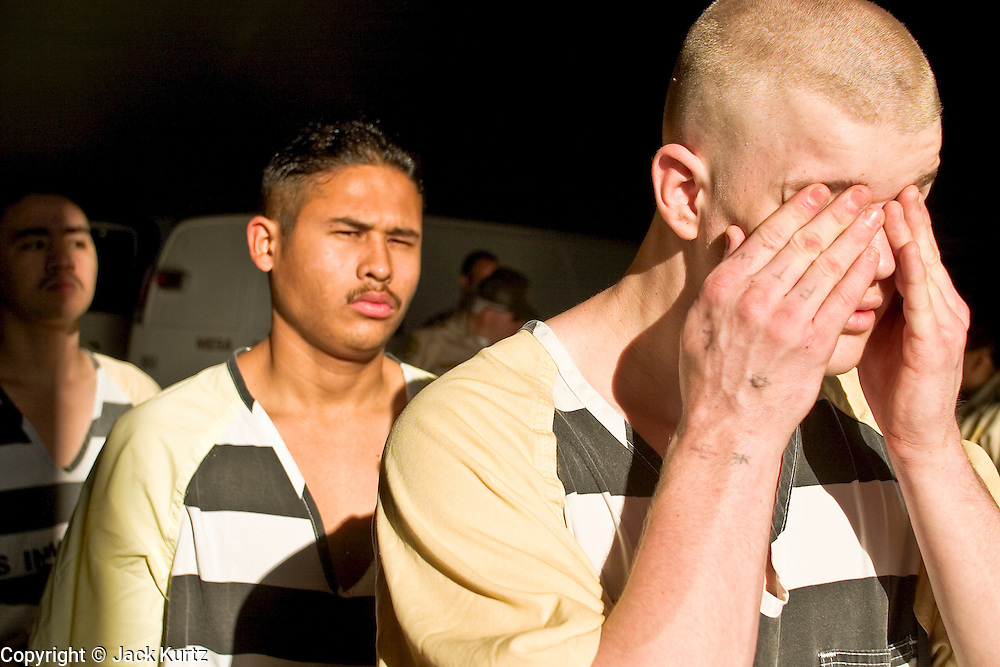 """24 MARCH 2004 - PHOENIX, AZ, USA: Members of the Maricopa County juvenile chain gang walk out of the jail into the morning sun in Phoenix, AZ, March 24, 2004. The juveniles volunteer to serve Maricpoa County Sheriff Joe Arpaio's chain gang. The sheriff, who claims to be """"the toughest sheriff in America,"""" has chain gangs in both the men's and women's jails and now has a chain gang for juveniles sentenced and serving time as adults in the county jail system. The sheriff claims it is the only juvenile chain gang in the country.   PHOTO BY JACK KURTZ"""