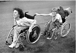 Young girls with physical impairments chasing each other in wheelchairs,