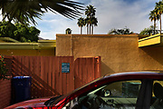 """Car parked in Palm Springs driveway with sign """"hippies use the back door"""""""