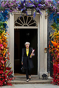 Prime Minister Theresa May leaves 10 Downing Street in Central London, United Kingdom on 3rd July 2019 to attend Prime Ministers Questions. The front door of No 10 Downing Street is decorated in rainbow coloured fresh flowers to celebrate the LGBTI community ahead of Pride weekend.
