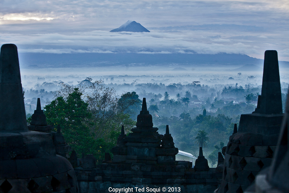 Mt. Merapi.<br /> The world's largest Buddhist Temple, Boroburdur, located in Central Java, Indonesia. The 9th century temple draws thousands of visitors a year who come to pilgrimage and see the amazing bas-reliefs and views. Boroburdur is surround by three volcanoes, most notably Mt Merapi which is still very active.