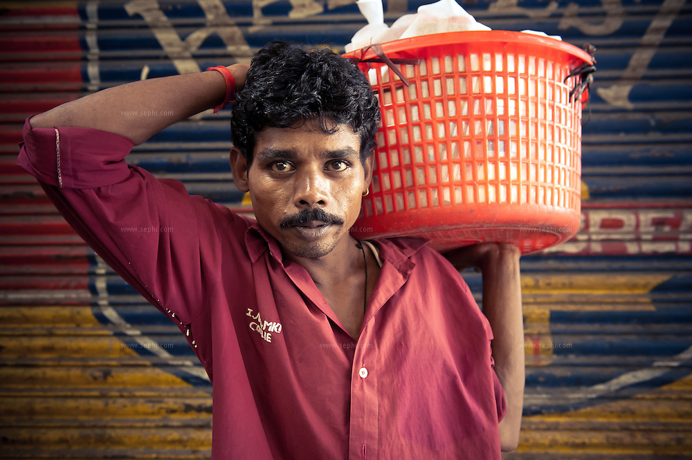 An Indian man carries a shopper's basket at INA market new delhi. The market is frequented by many foreigners and expats for its variety of imported products.