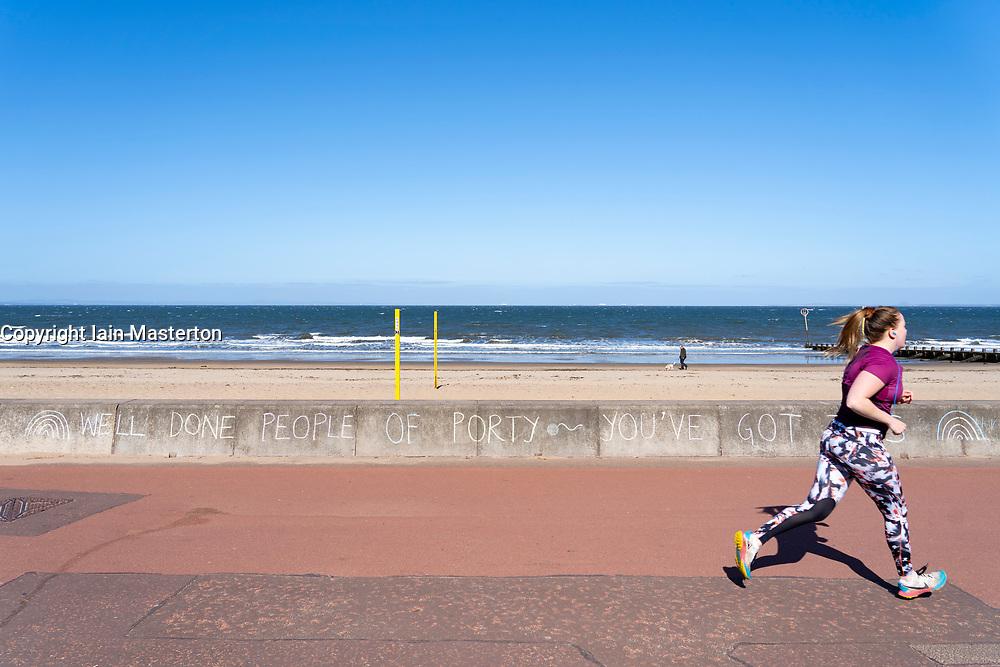 Portobello beach and promenade near Edinburgh during Coronavirus lockdown on 19 April 2020. Message of support chalked to seawall.