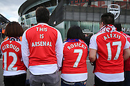 a Group of  Arsenal fans from Hong Kong wearing their team colours outside the Emirates Stadium before k/o. Barclays Premier league match, Arsenal v Crystal Palace at the Emirates Stadium in London on Sunday 17th April 2016.<br /> pic by John Patrick Fletcher, Andrew Orchard sports photography.