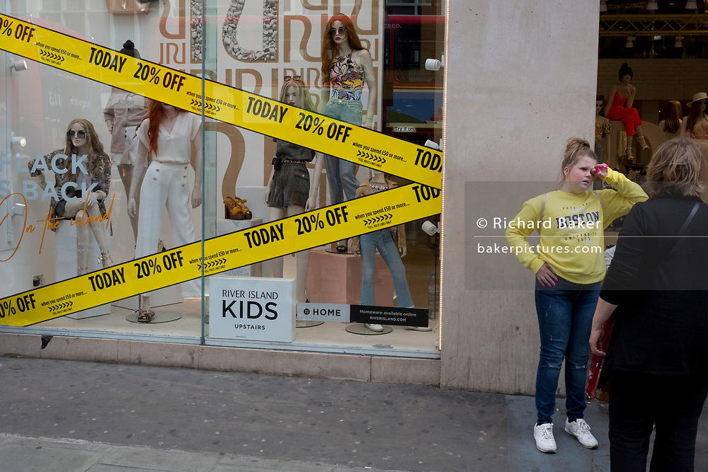 A teenager stands next to a shop promising 20% discounts on Oxford Street, on 30th May 2019, in London, England.