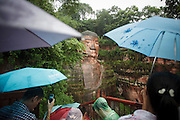 Tourists in the rain visiting the largest Buddha statue in the world, in Leshan, in Sichuan province.