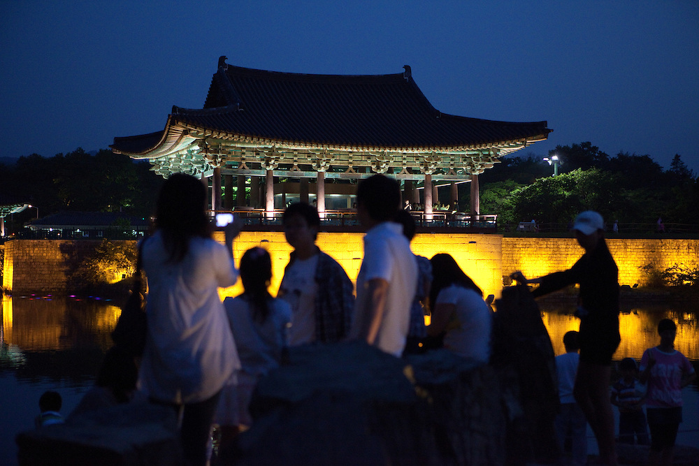 """People enjoying an evening at Anapji pond in the city of Gyeongju. Gyeongju was the capital of the ancient kingdom of Silla (57 BC - 935 AD) which ruled most of the Korean Peninsula between the 7th and 9th centuries. A vast number of archaeological sites and cultural properties from this period remain in the city. Gyeongju is often referred to as """"the museum without walls"""". / Gyeongju, South Korea, Republic of Korea, KOR, 20th of May 2010."""
