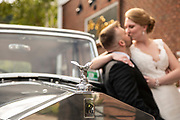 Wedding couple kissing in-front of a Rolls-Royce