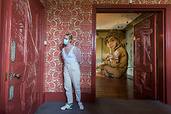 """© Licensed to London News Pictures. 22/07/2020. LONDON, UK. A staff member views a door by Vhils, with """"Silent Battle"""", 2020, by Berlin based duo HERAKUT in the background. Preview of """"disCONNECT"""", a new exhibition transforming a Victorian townhouse in Clapham Common, south west London displaying works by ten urban UK based as well as international artists.  The show is presented by Schoeni Projects, a new contemporary arts platform based in London and Hong Kong, and is accessible online and by appointment 24 July – 24 August 2020.  Photo credit: Stephen Chung/LNP"""