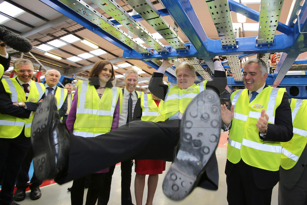© Licensed to London News Pictures. 29/02/2016. Antrim, Northern Ireland. Northern Ireland Secretary Theresa Villiers (3L) looks on as Mayor of London, Boris Johnson MP, swings under a chassis of a bus during a tour of Wrightbus plant in Antrim, Northern Ireland. Boris was visiting businesses that are supported by investment from Transport for London. Photo credit : Paul McErlane/LNP