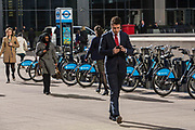 A city worker checks his mobile cell phone as he walks across the plaza outside Canary Wharf tube station in Docklands, London, United Kingdom. He walks past a Barclays bike park, nicknamed Boris bikes, which are a popular form of transport for Londoners.