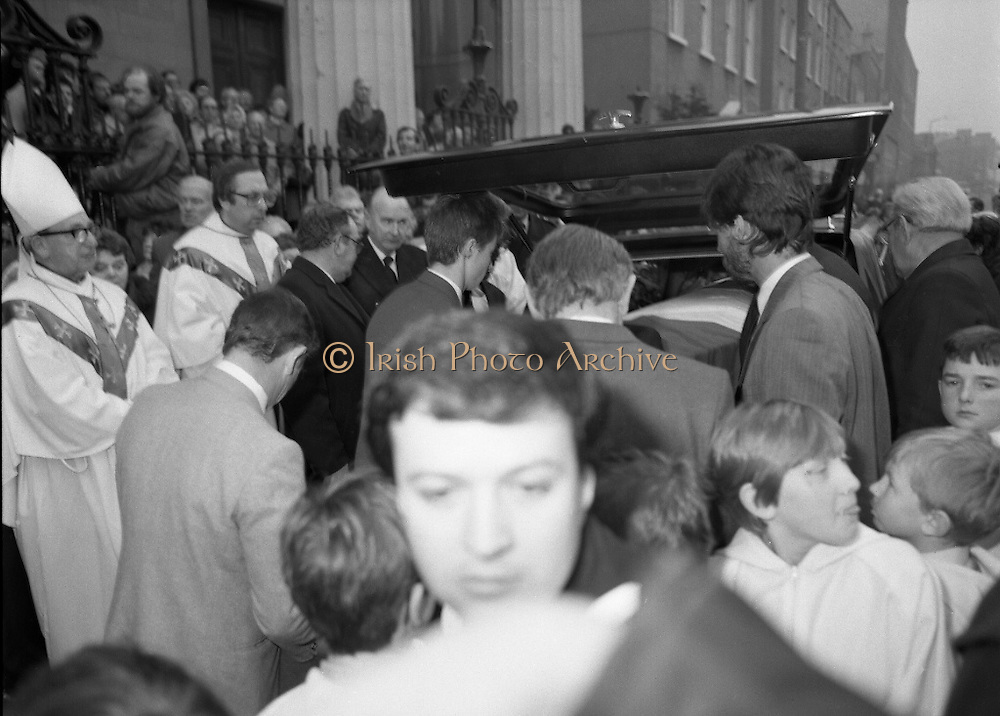 Funeral Of Sean McBride.   (R71)..1988..18.01.1988..01.18.1988..18th January 1988..Today saw the Funeral of Seán McBride.Seán MacBride was an Irish government minister, a prominent international politician and a former Chief of Staff of the IRA. His funeral took place from the Pro-Cathedral in Dublin to the family plot in Glasnevin Cemetery, Dublin.The Chief mourners were Tiernan McBride,son, Anna White,daughter and Declan White, son in law...Image shows the flag draped coffin of Seán McBride being placed into the hearse outside the Pro-Cathedral. President Patrick Hillery is seen amongst the mourners.