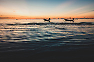 Ko Tao, Thailand - October 15, 2011: Two long-tail boats are anchored off of Sairee Beach on Ko Tao at sunset.