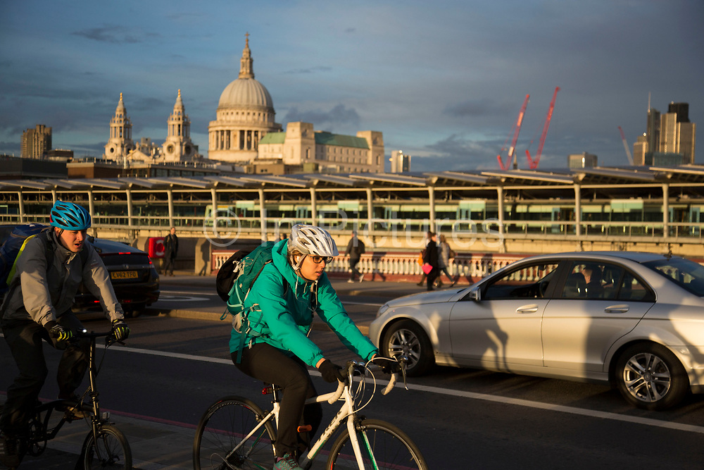 Commuters cycling across Blackfriars Bridge overlooking St Pauls Cathedral in London, England, United Kingdom. Cycling has become a very popular mode of transport in the capital as people try to avoid public transport, saving money, getting fit and saving time.