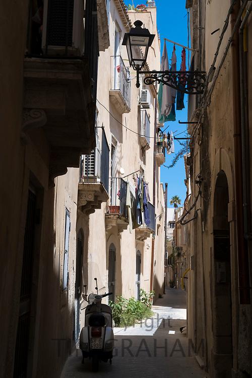 Motorscooter, balconies, lantern and laundry in street scene in alleyway in Greek Streets by via Della Giudecca, Ortigia, Syracuse, Sicily