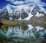Snow-covered Rondoy Peak (5870 m or 19,260 feet) reflects in a tarn (mountain pond) in the Cordillera Huayhuash, Andes Mountains, Peru, South America. Panorama was stitched from 2 overlapping photos.