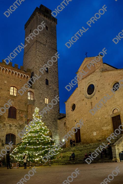 San Gimignano, Italy - December 29, 2018 Illuminated Natural christmas tree and Duomo from town square
