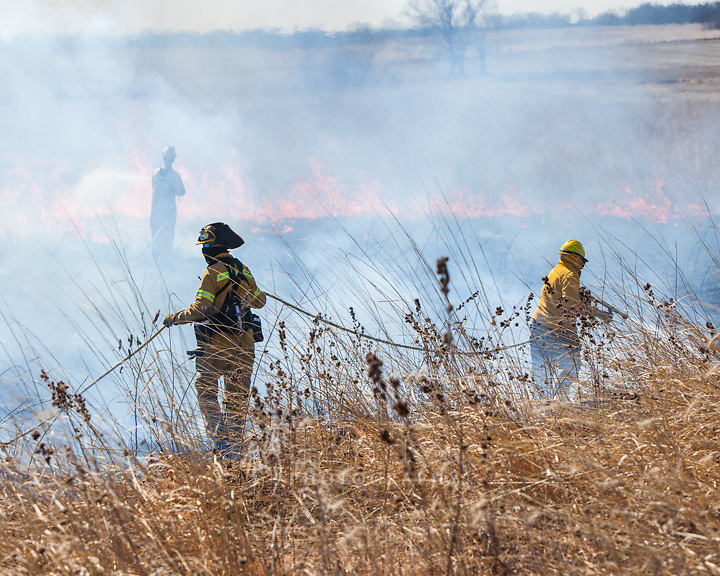 At a prairie burn, teamwork is required between the hose manager and the sprayer.
