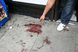 © Licensed to London News Pictures. 25/04/2019. London, UK. A man points at the blood stains outside Hill's New Point newsagent on Leytonstone High Road, Waltham Forest in East London. Two men were stabbed multiple times at a bus stop next to Hill's New Point newsagent close to Leytonstone High Road overground station just before 8pm on Wednesday 24 April 2019. A man in his 20s remains in a hospital in a critical condition. Photo credit: Dinendra Haria/LNP