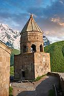 Pictures & images of Gergeti Holy Trinity (Tsminda Sameba) Georgian Orthodox and Apostolic Church bell tower, 14th century, Gergeti, Khevi province, Georgia (country). At Sunset.