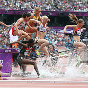Athletes tackle the water jump during round one of the Women's 3000m Steeplechase at the Olympic Stadium at Olympic Park, during the London 2012 Olympic games. London, UK. 4th August 2012. Photo Tim Clayton