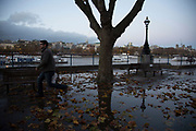 A man after jumping over Autumn leaves in a puddle of rain water on the Southbank riverside walkway, London, United Kingdom. The South Bank is a significant arts and entertainment district, and home to an endless list of activities for Londoners, visitors and tourists alike.