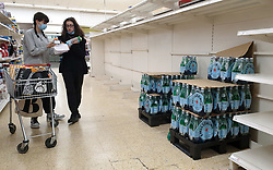 © Licensed to London News Pictures. 31/07/2021. London, UK. Shoppers wearing face coverings stand next to nearly-empty shelves of bottled drink water in Sainsbury's, north London. Record breaking numbers of people have been forced to self-isolate after being alerted by the NHS Covid-19 app. The pingdemic has seen staff shortages at supermarkets, resulting in less stock making its way to supermarket shelves. Labour leader Sir Keir Starmer has demanded that the government brings forward the end to self-isolation from 16 August to 7 August. Photo credit: Dinendra Haria/LNP