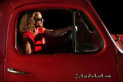 Man in shades in a classic red studebaker truck
