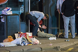 © Licensed to London News Pictures . 15/06/2014 . Manchester , UK . A men lies collapsed on the pavement surrounded by litter and supported by another man . People on a night out in Manchester City Centre overnight , following England's defeat to Italy in the World Cup . Photo credit : Joel Goodman/LNP