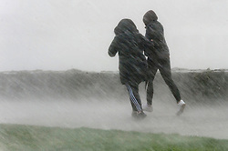© Licensed to London News Pictures. 09/02/2020. Porthcawl, Bridgend, Wales, UK. People get caught in a torrential downpour with severe gale force winds at Trecco Bay in the Welsh seaside resort of Porthcawl in Bridgend, UK. Photo credit: Graham M. Lawrence/LNP