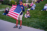 20 SEPTEMBER 2020 - DES MOINES, IOWA: A man waves an American flag during a vigil for Supreme Court Justice Ruth Bader Ginsburg in Poppajohn Sculpture Park in Des Moines. About 200 people attended the candlelight vigil for Justice Ruth Bader Ginsburg. Ginsburg died from pancreatic cancer on September 18, 2020.      PHOTO BY JACK KURTZ