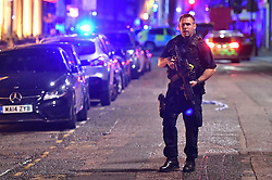 """Armed police on Borough High Street as police are dealing with a """"major incident"""" at London Bridge."""