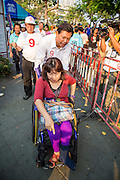 17 FEBRUARY 2013 - BANGKOK, THAILAND:  Pheu Thai gubernatorial candidate PONGSAPAT PONGCHAREON hels a woman in a wheelchair during a campaign rally in Bangkok Sunday. Pol General Pongsapat Pongcharoen, a former deputy national police chief who also served as secretary-general of the Narcotics Control Board is the Pheu Thai Party candidate in the upcoming Bangkok governor's election. (He resigned from the police force to run for Governor.) Former Prime Minister Thaksin Shinawatra reportedly recruited Pongsapat. Most of Thailand's reputable polls have reported that Pongsapat is leading in the race and likely to defeat Sukhumbhand Paribatra, the Thai Democrats' candidate and incumbent. The loss of Bangkok would be a serious blow to the Democrats, whose base is the Bangkok area.     PHOTO BY JACK KURTZ