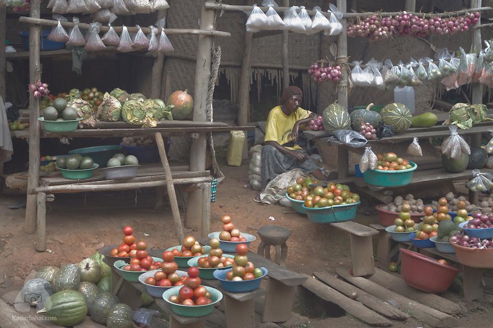 Woman sitting at her roadside vegetable stalls, Uganda