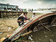 04 NOVEMBER 2015 - YANGON, MYANMAR: Workers repair the hull of a small wooden ferry on the banks of the Yangon River in Dala, Yangon is in the background. Dala is located on the southern bank of Yangon River across from downtown Yangon, Myanmar. Many Burmese live in Dala and surrounding communities and go across the river into central Yangon for work. Before World War 2, the Irrawaddy Flotilla Company had its main shipyards in Dala. That tradition lives on in the small repair businesses the work on the hundreds of small wooden boats that serve as commuter ferries for the people of Yangon. The boats are pulled up onto the riverbank in Dala and repaired by hand.    PHOTO BY JACK KURTZ