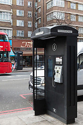 Just yards apart on either side of the road, modern public telephones carrying illuminated advertising add to the clutter of signs, lampposts, sandwich boards, bus shelters and street furniture on Edgeware Road in London. LONDON, February 12 2019.