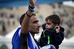 November 12, 2017 - Athens, Attica, Greece - Merousis Hristoforos covered with the greek flag holds his son at the 35th Athens Classic Marathon in Athens, Greece, November 12, 2017. (Credit Image: © Giorgos Georgiou/NurPhoto via ZUMA Press)