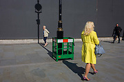Women with a lamp post shadow against a grey construction hoarding in central London's Trafalgar Square. Painting work is being carried out to the street lighting lamp post, a green plastic fence surrounding the wet paint while the post's upright has created a strong linear theme to the pavement and background hoarding that screens other work.