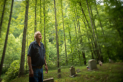 "Near his home in Bandytown, West Virginia, Leo Cook visits the Webb Cemetery, where several of his relatives are buried. Bandytown is in the heart of America, where mountaintop-removal mines are abundant. Mining firms must maintain a 100-foot protective zone around such burial grounds. Mountaintop Removal is a method of surface mining that literally removes the tops of mountains to get to the coal seams beneath. It is the most profitable mining technique available because it is performed quickly, cheaply and comes with hefty economic benefits for the mining companies, most of which are located out of state. Many argue that they have brought wage-paying jobs and modern amenities to Appalachia, but others say they have only demolished an estimated 1.4 million acres of forested hills, buried an estimated 2,000 miles of streams, poisoned drinking water, and wiped whole towns from the map. The mountaintop-removal mine near Blair caused the population to fall from 700 in the 1990s to fewer than 50 today, according to the Blair Mountain Heritage Alliance. ""I saw Lindytown disappear,"" Leo Cook said. ""Three people up there that died, and I believe in my soul -- I'll go to my grave believin' this?that aggravation's what caused it."" © Ami Vitale"
