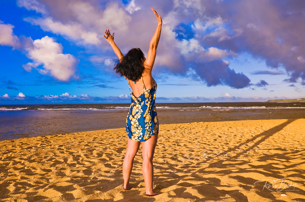 Woman raising arms on Tunnels Beach at sunset, Island of Kauai, Hawaii