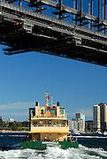 Ferry sailing beneath Sydney Harbour Bridge. Sydney, Australia
