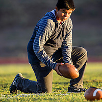Dillon Tachine lines up footballs on the field for the Tohatchi Cougars as they were warming up for their match with the Wingate Bears Friday at Wingate High School.