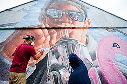 Graffiti artists 'Fanakapan' (left) and 'Insane5' work on a huge mural on a house as they take part in Upfest, a street art and graffiti festival in Bristol.
