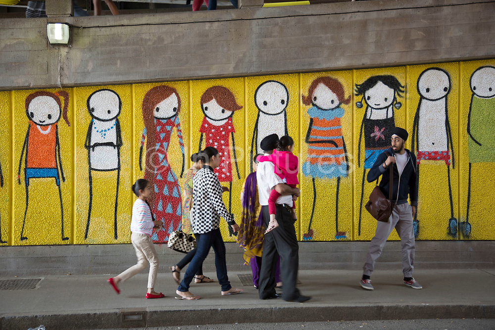 Street art graffiti piece showing characters growing up by artist Stik. on the Southbank, London, UK. Stik has painted the walkway underneath the Hungerford Railway Bridge in Waterloo with a whole crowd of his famous Stik men. The South Bank is a significant arts and entertainment district, and home to an endless list of activities for Londoners, visitors and tourists alike.