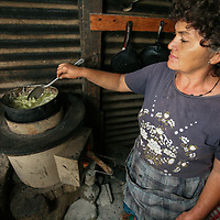Francisca Ramírez cooking izote flowers on an ecological stove provided in a programme paid for with the fairtrade premium. The stove cooks a meal with a couple of small sticks, saving firewood, and making life easier for Francisca. Cooperativa Los Pinos is a certified Fairtrade producer based in El Salvador.
