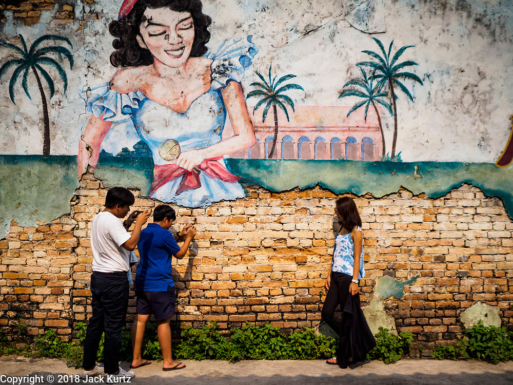 22 DECEMBER 2018 - CHANTABURI, THAILAND: Thai tourists take portraits of each other in front of a mural in Chantaburi. Chantaburi is the capital city of Chantaburi province on the Chantaburi River. Because of its relatively well preserved tradition architecture and internationally famous gem market, Chantaburi is a popular weekend destination for Thai tourists.         PHOTO BY JACK KURTZ