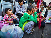 30 AUGUST 2016 - BANGKOK, THAILAND: People sit in the street behind the Poh Teck Tung Shrine after getting food and clothing on the last day of Hungry Ghost Month in Bangkok. Chinese temples and shrines in the Thai capital host food distribution events during Hungry Ghost Month, during the 7th lunar month, which is usually August in the Gregorian calendar.         PHOTO BY JACK KURTZ