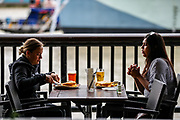 Two friends appear to be having lunch and drinks nearby the River Thames in Central London on Saturday, July 4, 2020. As Britain lifts its Covid-19 Lockdown Measures Pubs reopen today welcoming back customers for the first time in more than three months. (VXP Photo/ Vudi Xhymshiti)
